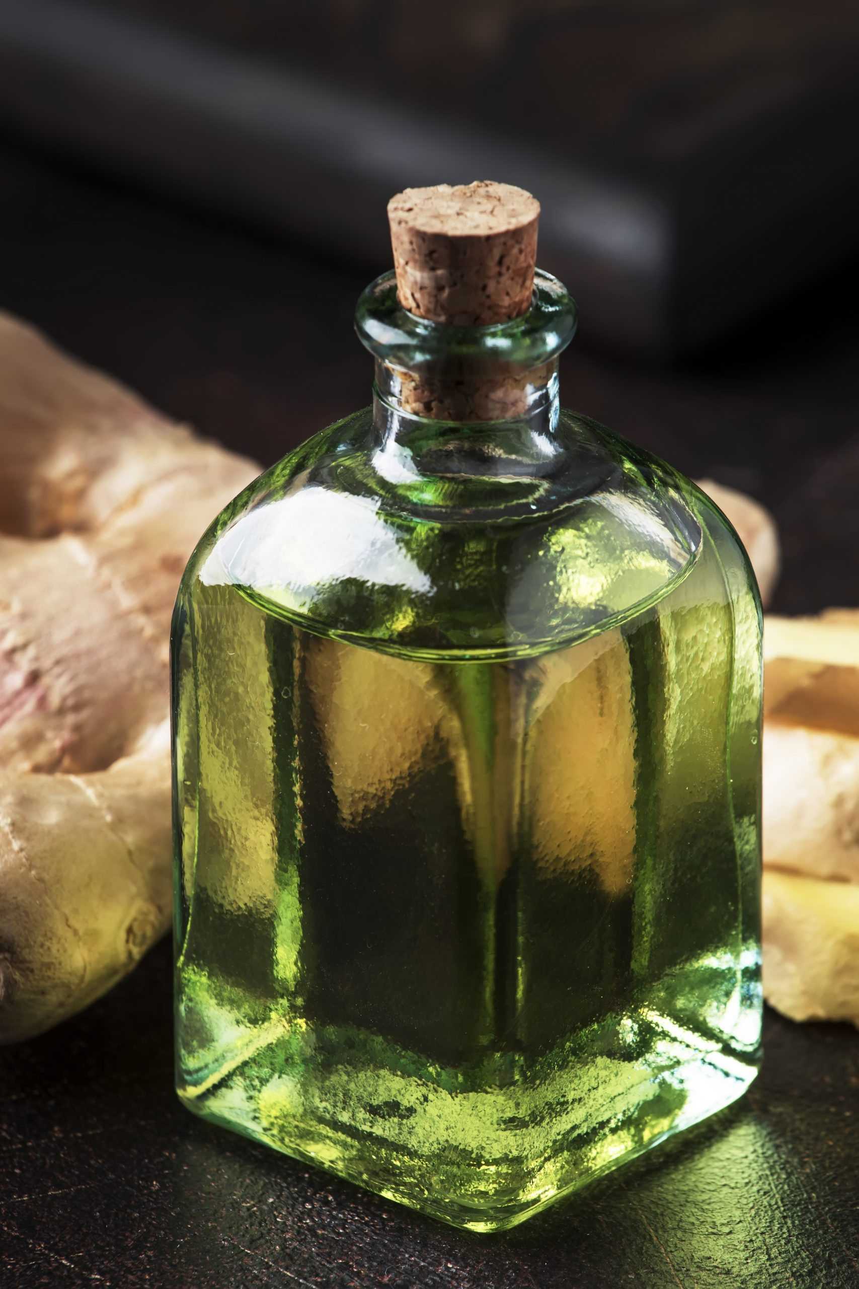 Ginger oil and fresh ginger root, dark table, selective focus